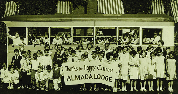 Children pose in front of a trolley car at the Times Country Camp